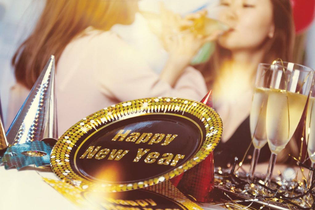 A decorative bowl with HAPPY NEW YEAR printed on it. In the background, two women drink champagne.