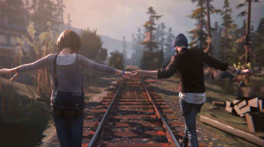 two girls hold hands as they walk along a railway line